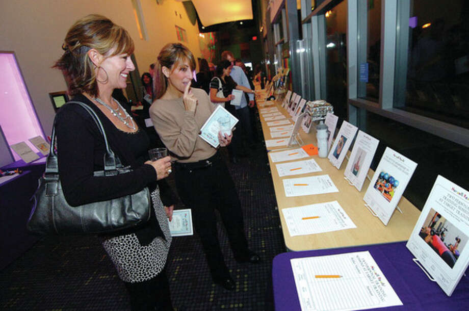 Hour Photo Alex von Kleydorff; l-r Stacey Brekke and Ronnie Stanford bid on silent auction items up for grabs at Norwalk reads fundraiser gala at Stepping Stones. / 2012 The Hour Newspapers
