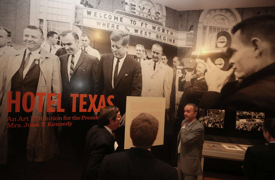 """Curator Olivier Meslay, right, speaks with others at the entrance of the exhibit """"Hotel Texas: An Art Exhibition for the President and Mrs. John F. Kennedy,"""" during a press preview at the Dallas Museum of Art Wednesday, May 22, 2013, in Dallas. The exhibit reunites 14 of the 16 works that were placed in Suite 850 for the Kennedys' one-night stay in Fort Worth and includes photos of the suite before and after the artwork was placed there, video footage of the room being prepared for the Kennedys and historical artifacts from the visit, including a sign welcoming the Kennedys to Texas. (AP Photo/LM Otero) / AP"""