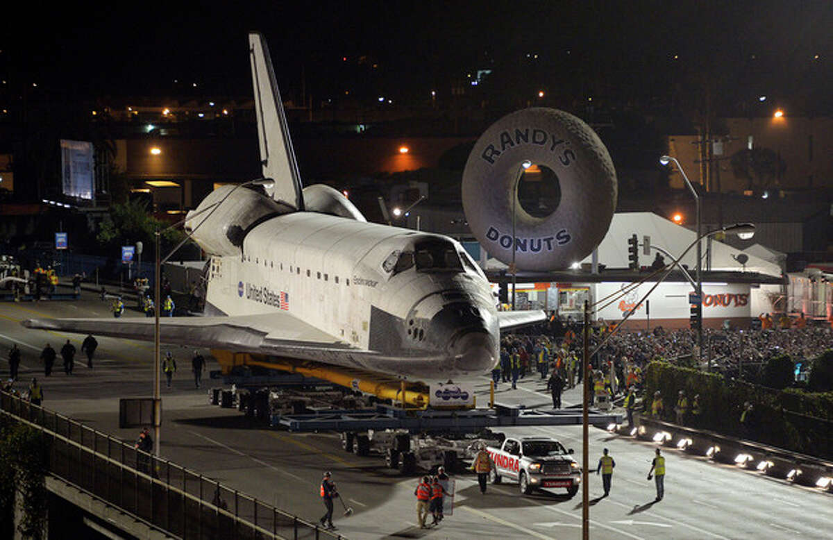 The Space Shuttle Endeavour is slowly moved across Interstate 405 by a Toyota Tundra, Friday, Oct.12, 2012, in Los Angeles. The shuttle is on its last mission ?- a 12-mile creep through city streets. It will move past an eclectic mix of strip malls, mom-and-pop shops, tidy lawns and faded apartment buildings. Its final destination: California Science Center in South Los Angeles where it will be put on display. (AP Photo/Mark J. Terrill)