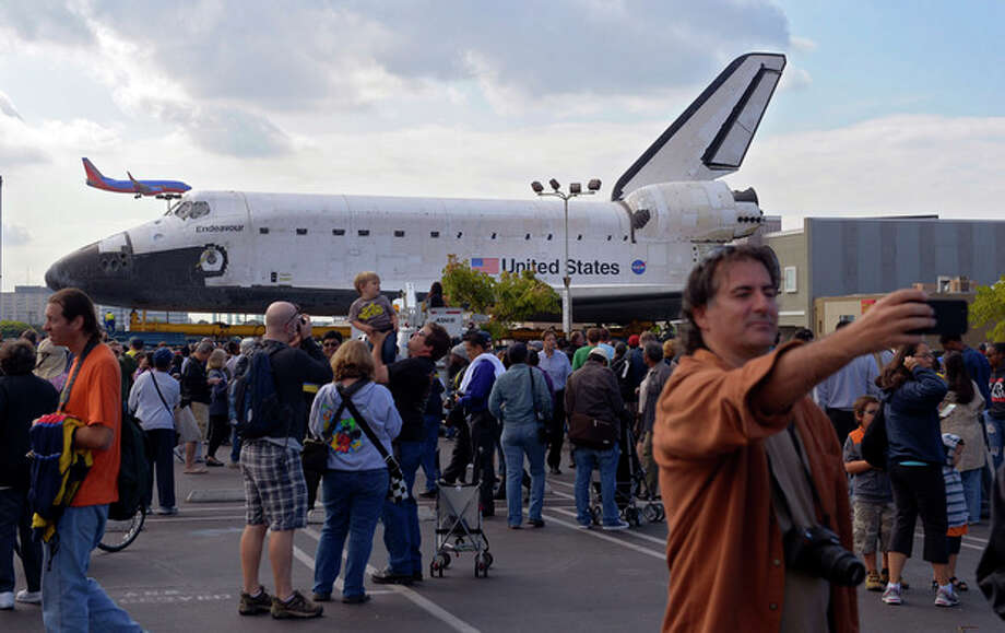 """Spectators gather around the Space Shuttle Endeavour before it is moved along city streets, Friday, Oct.12, 2012, in Los Angeles. Endeavour's two-day, 12-mile road trip to the California Science Center, where it will be put on display, kicked off early Friday. Rolled on a 160-wheeled carrier, it left from a hangar at the Los Angeles International Airport, passing diamond-shaped """"Shuttle Xing"""" signs, and reached city streets about two hours later. (AP Photo/Mark J. Terrill) / AP"""