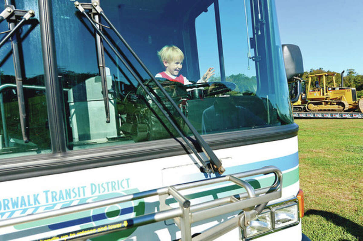 John Morse, 3, gets behind the wheel of a Transit bus during the first Annual KidzFest Touch-A-Truck Fundraiser will take place at Taylor Farm Park in Norwalk to benefit the Children's Connection Saturday, Hour photo / Erik Trautmann