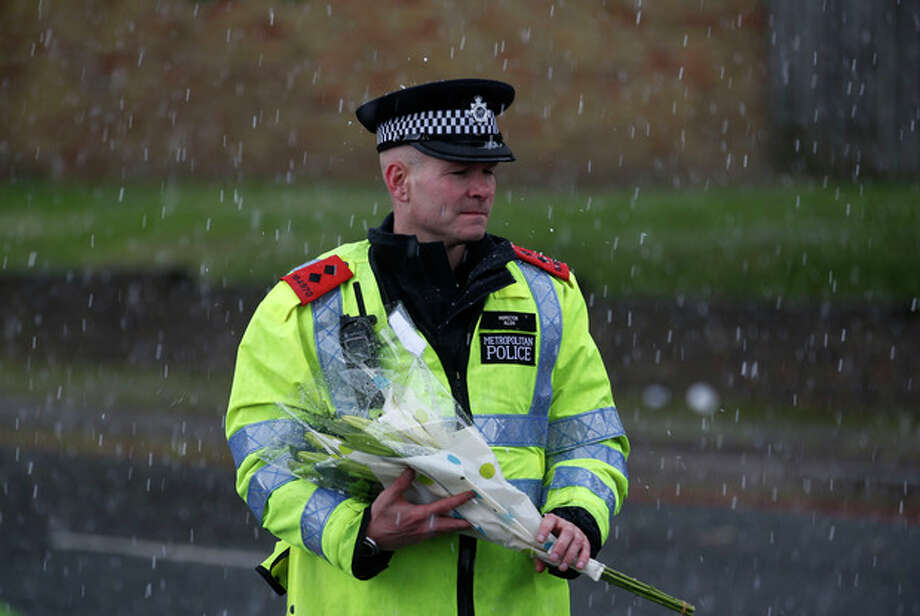 A police officer holds a floral tribute handed to him by a member of the public to be placed at the scene of a terror attack in Woolwich, southeast London, Thursday, May 23, 2013. The British government's emergency committee met Thursday after two attackers killed a man in a daylight attack in London that raised fears terrorism had returned to the capital. (AP Photo/Sang Tan) / AP