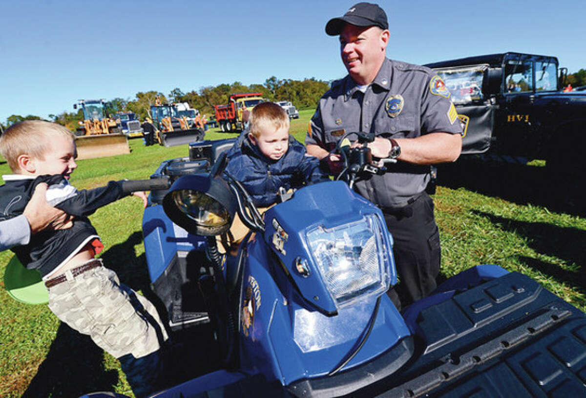 Hour photo / Erik Trautmann Mathew and Andrew Martino get a ride on Weston Police Sgt. Pat Tauber's motorcycle during the first-ever KidzFest Touch-A-Truck Fundraiser Saturday at Taylor Farm Park in Norwalk to benefit the Children's Connection.