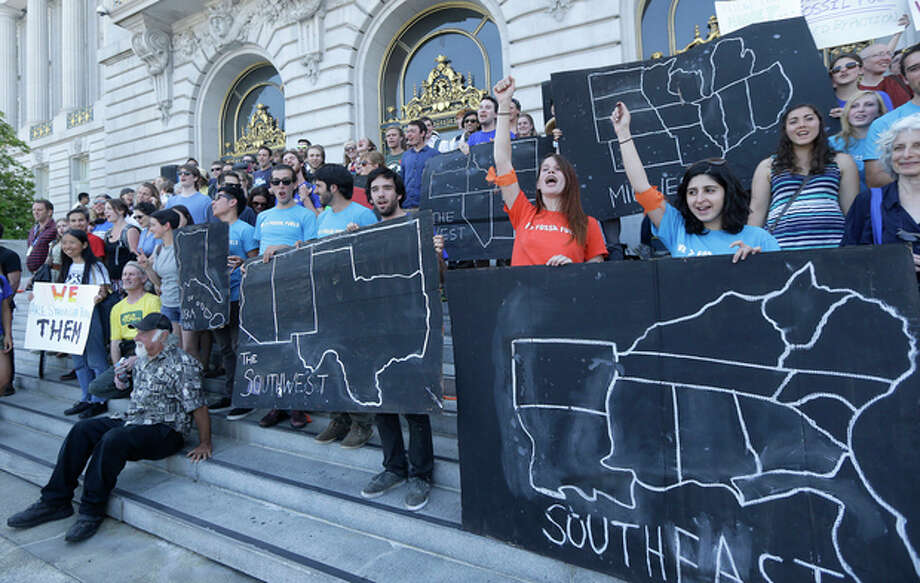 College students and supporters hold up signs at a rally to support fossil fuel divestment outside of City Hall in San Francisco, Thursday, May 2, 2013. In an effort to slow the pace of climate change, students at more than 200 colleges are asking their schools to stop investing in fossil fuel companies. (AP Photo/Jeff Chiu) / AP