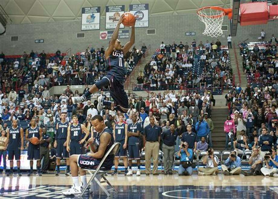 Connecticut's Ryan Boatright, top, leaps over teammate Shabazz Napier during the slam dunk competition at the NCAA college basketball team's First Night event in Storrs, Conn., Friday, Oct. 12, 2012. Omar Calhoun won the competition. (AP Photo/Jessica Hill) / FR125654 AP