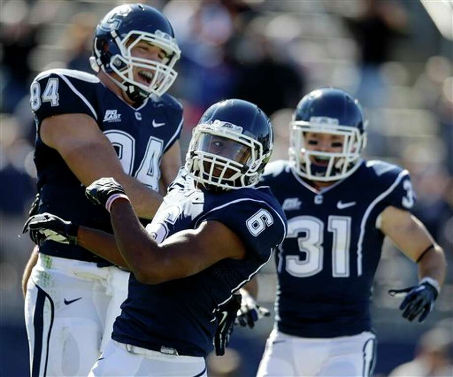Connecticut wide receiver Michael Smith (6) celebrates his touchdown with teammates tight end Ryan Griffin (94) and wide receiver Nick Williams (31) in the first quarter of an NCAA football game against Temple in East Hartford, Conn., Saturday, Oct. 13, 2012. (AP Photo/Michael Dwyer) / AP