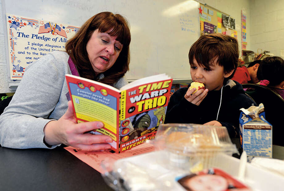 UBSemployee Susan Hoppe eats lunch and reads a Time Warp Trio story with Stark Elementary School 3rd graders including Brayn Guzman as part of the Stamford Public Schools Power Lunch Program which looks to increase children's' success in school and life through one-to-one reading experiences with caring adults at lunchtime. Hour photo / Erik Trautmann / (C)2012, The Hour Newspapers, all rights reserved