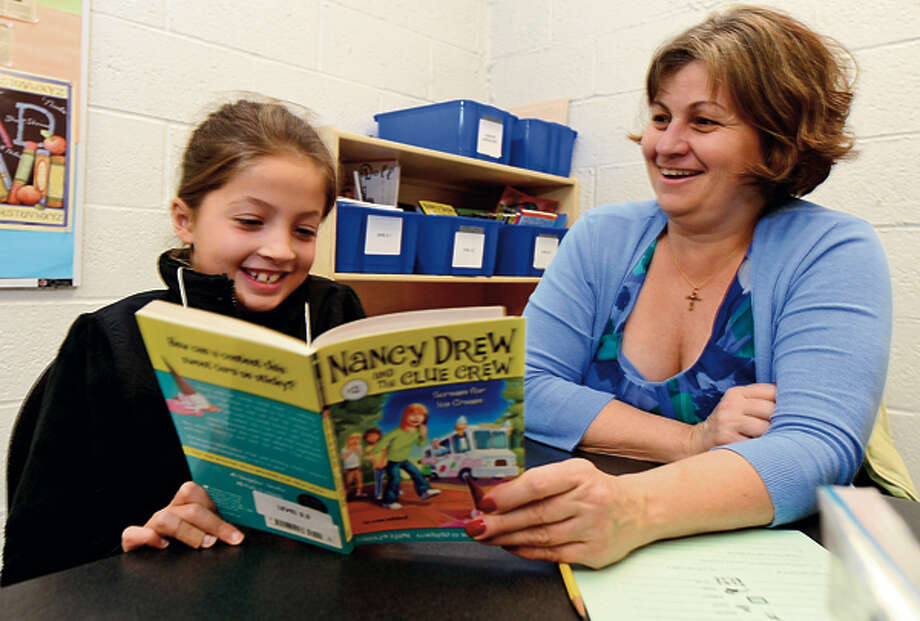 UBSemployee Theresa Potenza eats lunch and reads a Nancy Drew mystery with Stark Elementary School 3rd grader, Jullia Salerno, as part of the Stamford Public Schools Power Lunch Program which looks to increase children's' success in school and life through one-to-one reading experiences with caring adults at lunchtime. Hour photo / Erik Trautmann / (C)2012, The Hour Newspapers, all rights reserved