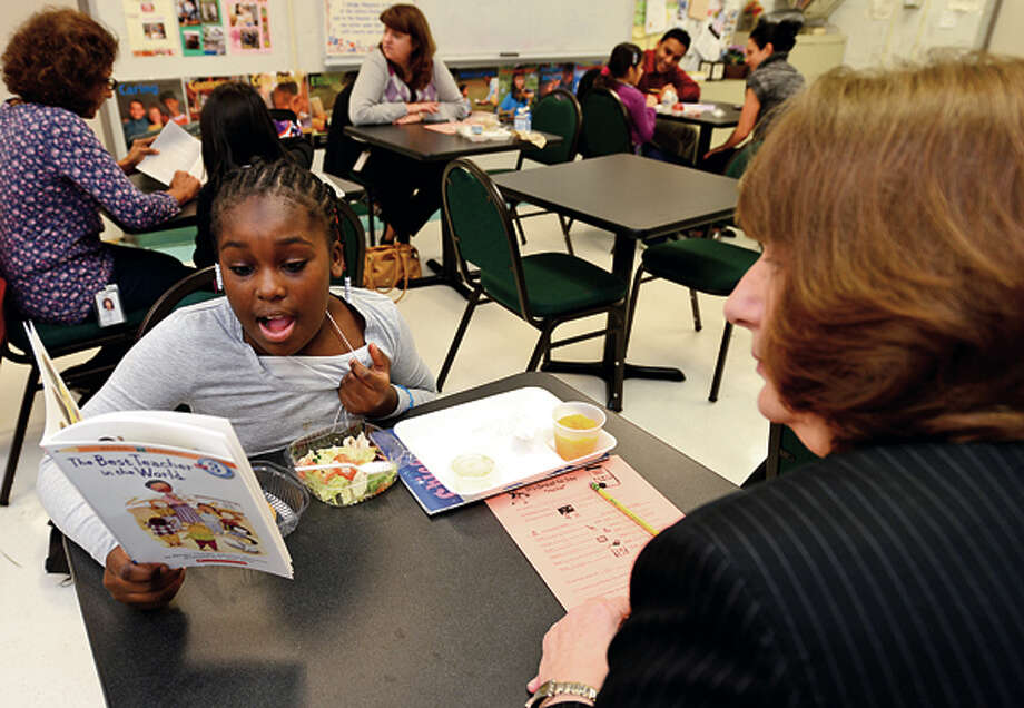 UBSemployee Linda Cook eats lunch and reads with Stark Elementary School 3rd grader Aria Haughton as part of the Stamford Public Schools Power Lunch Program which looks to increase children's' success in school and life through one-to-one reading experiences with caring adults at lunchtime. Hour photo / Erik Trautmann / (C)2012, The Hour Newspapers, all rights reserved