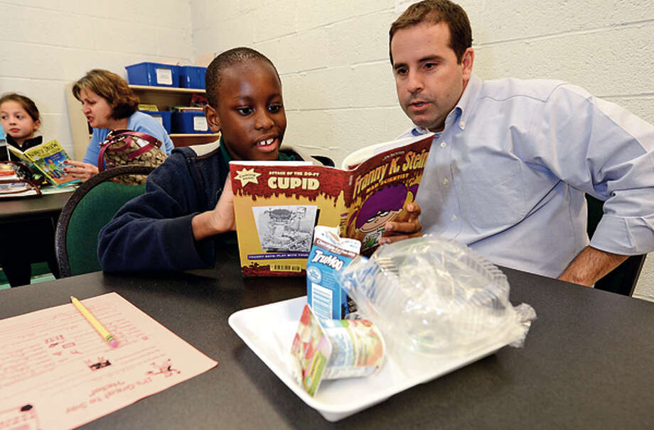 UBS employee Matt Delawder eats lunch and reads a Franny K. Stein story with Stark Elementary School 3rd grader Joshua DeQuene as part of the Stamford Public Schools Power Lunch Program which looks to increase children's' success in school and life through one-to-one reading experiences with caring adults at lunchtime. Hour photo / Erik Trautmann / (C)2012, The Hour Newspapers, all rights reserved