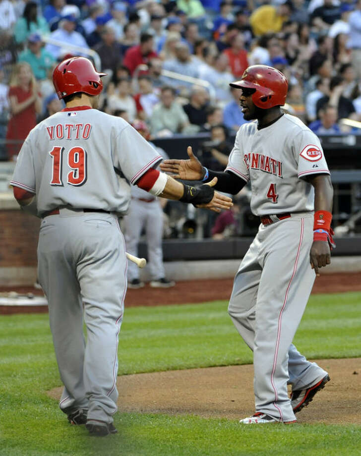 Cincinnati Reds' Brandon Phillips (4) is greeted at home plate by Joey Votto (19) after they both scored on a fielding error by New York Mets third baseman David Wright in the first inning of a baseball game at Citi Field on Tuesday, May 21, 2013 in New York. (AP Photo/Kathy Kmonicek)
