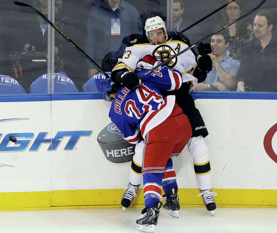 New York Rangers' Ryan Callahan (24) checks Boston Bruins' Chris Kelly (23) during the first period in Game 3 of the Eastern Conference semifinals in the NHL hockey Stanley Cup playoffs in New York, Tuesday, May 21, 2013. (AP Photo/Frank Franklin II) / AP