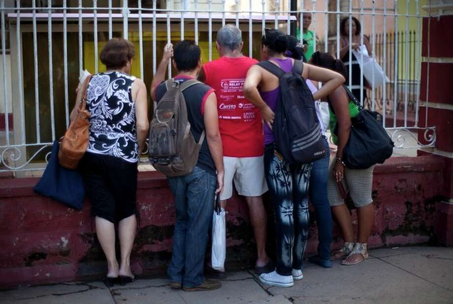 People read adjustments to the migratory policy, posted on a wrought iron fence of an immigration office in Havana, Cuba, Tuesday, Oct 16, 2012. The Cuban government announced Tuesday that it will no longer require islanders to apply for an exit visa, eliminating a much-loathed bureaucratic procedure that has been a major impediment for many seeking to travel overseas for more than a half-century. (AP Photo/Ramon Espinosa) / AP