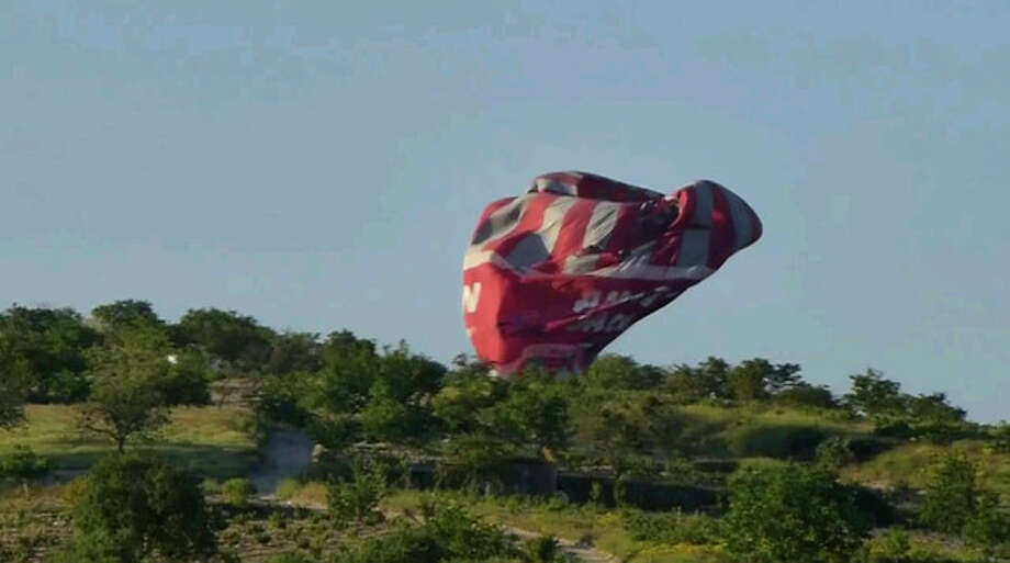 This image from video provided by E. Wayne Ross shows an Anatolian Balloons Company hot air balloon crashing near Göreme National Park and the Rock Sites of Cappadocia in central Turkey, Monday May 20 2013. Two hot air balloons collided in mid-air during a sightseeing tour of volcanic rock formations in Turkey on Monday, causing one of them to crash to the ground, officials said. One Brazilian tourist was killed while 24 other people on board were injured. (AP Photo/E. Wayne Ross) / E. Wayne Ross