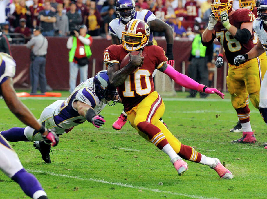 Washington Redskins quarterback Robert Griffin III (10) gets away from Minnesota Vikings safety Harrison Smith (22) to score a touchdown during the first half of an NFL football game, Sunday, Oct. 14, 2012, in Landover, Md. (AP Photo/Richard Lipski) / FR170623 AP