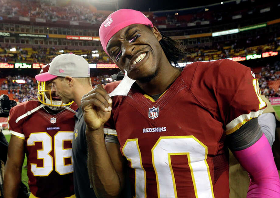 Washington Redskins quarterback Robert Griffin III (10) pulls tape off his chin after an NFL football game against the Minnesota Vikings, Sunday, Oct. 14, 2012, in Landover, Md. The Redskins won 38-26. (AP Photo/Pablo Martinez Monsivais) / AP