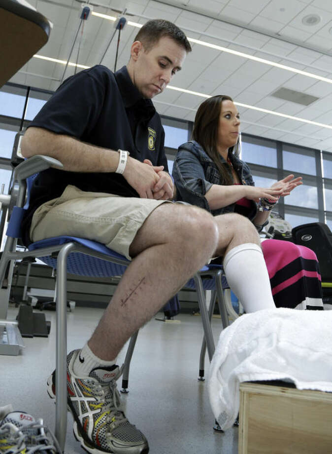 MBTA Police Officer Richard Donahue listens as his wife, Kim, speaks during an interview at Spaulding Rehabilitation Hospital in Boston's Charlestown section, Sunday, May 19, 2013. Donahue almost lost his life after being shot during the crossfire with the Boston Marathon bombing suspects in Watertown, Mass. (AP Photo/Elise Amendola)