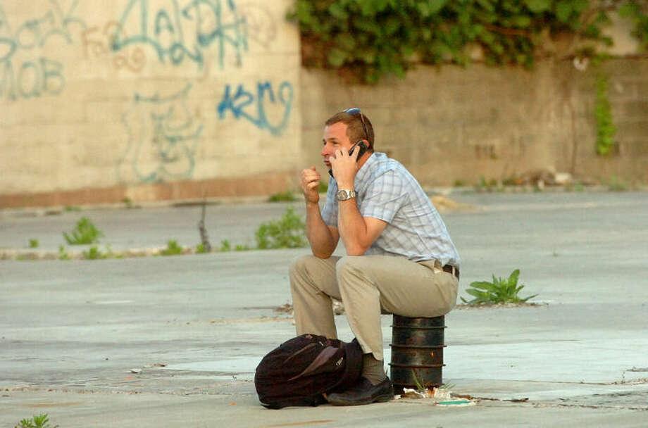 Hour Photo/Alex von Kleydorff. A stranded passnger talks on his cell phone