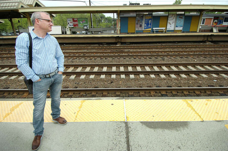 Hour Photo/Alex von Kleydorff . Ed Bocchino watches to the east for a train arriving onTrack 4 at The Westport Train Station on Monday morning. Headed to New York from Fairfield he had to take a bus from Fairfield Metro station then board a train in Westport to finish the trip.