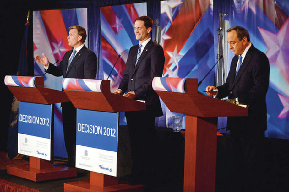 Congressman Jim Himes, center, and republican challenger Steve Obstinik, left, debate at the Norwalk Inn Thursday afternoon with the assiatnce of moderator John Appleby of News12.Hour photo / Erik Trautmann / (C)2012, The Hour Newspapers, all rights reserved