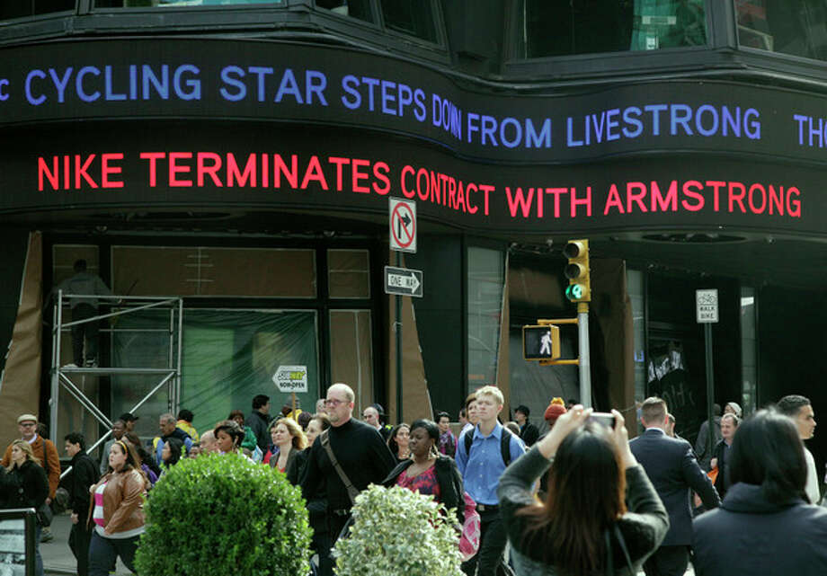 Headlines about cyclist Lance Armstrong scroll above people in New York's Times Square, Wednesday, Oct. 17, 2012. Armstrong stepped down as chairman of his Livestrong cancer-fighting charity and Nike severed ties with him as fallout from the doping scandal swirling around the famed cyclist escalated Wednesday. (AP Photo/Richard Drew) / AP