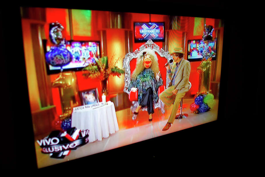 """In this Oct. 17, 2012, a TV show called """"La Comay"""" (roughly translated to """"The Godmother""""), is seen on a TV set in San Juan, Puerto Rico. This five-foot tall puppet with outlandish red lips, a shrill voice and a penchant for salacious details rules Puerto Rico's gossip circuit, with legions tuning into her show every afternoon ready for the latest bombshell. And La Comay dishes it out with ominous music playing in the background, talking about everyone from Mexican crooner Luis Miguel to Puerto Rico's own Miss Universe beauty queen Zuleyka Rivera. (AP Photo/Ricardo Arduengo) / AP"""