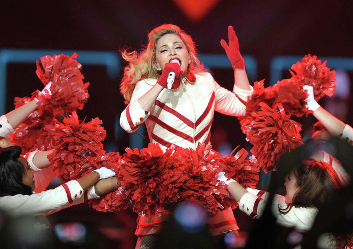 """FILE - This Oct. 10, 2012 file photo shows Madonna performing on the """"MDNA"""" tour at Staples Center in Los Angeles. Some Colorado fans are upset after music superstar Madonna used guns during a performance. Madonna started her show Thursday, Oct. 18, at the Pepsi Center in Denver with a gun scene, which she has used in previous performances. TV station KUSA received several calls Friday from concert-goers saying they were offended she used guns and violence as part of her show in light of recent events in the state that included a mass shooting at a theater during a Batman movie on July 20 that left 12 people dead. (Photo by John Shearer/Invision/AP, file)"""