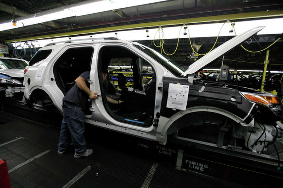 FILE - In this Dec. 1, 2010 file photo, plant employees assemble a 2011 Ford Explorer on the assembly line at Ford's Chicago Assembly Plant. Ford Motor Co. said Wednesday, May 22, 2013 that 21 of its North American factories will shut for only one week this summer. That includes the Chicago plant that makes the Ford Explorer SUV and the Mexican plant that makes the Fusion sedan. (AP Photo/M. Spencer Green, File) / AP