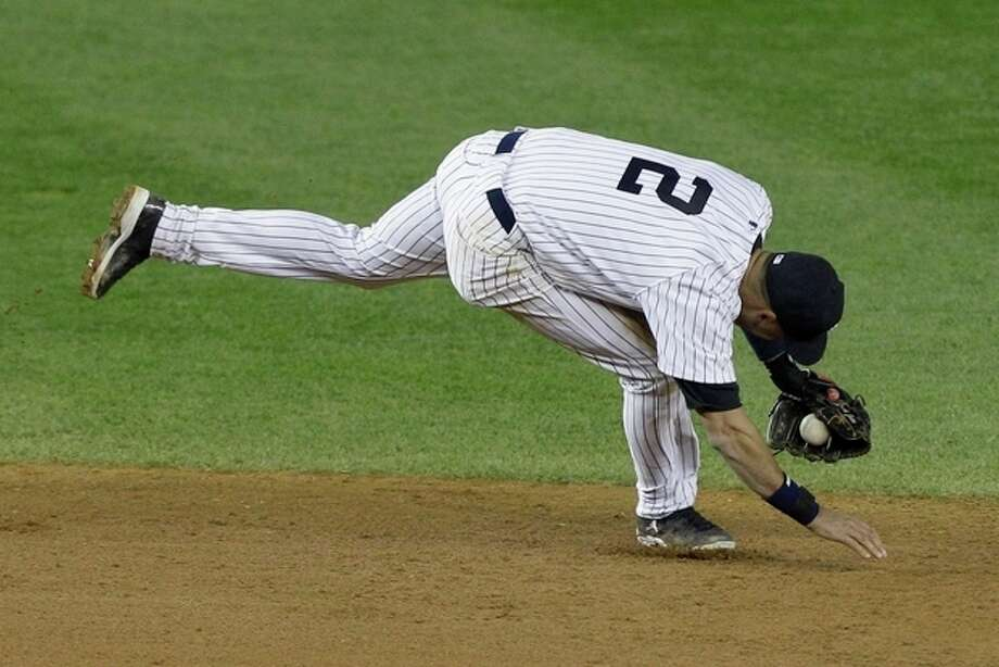 New York Yankees shortstop Derek Jeter injures himself fielding a ball in the 12th inning of Game 1 of the American League championship series against the Detroit Tigers early Sunday, Oct. 14, 2012, in New York. (AP Photo/Kathy Willens) / AP