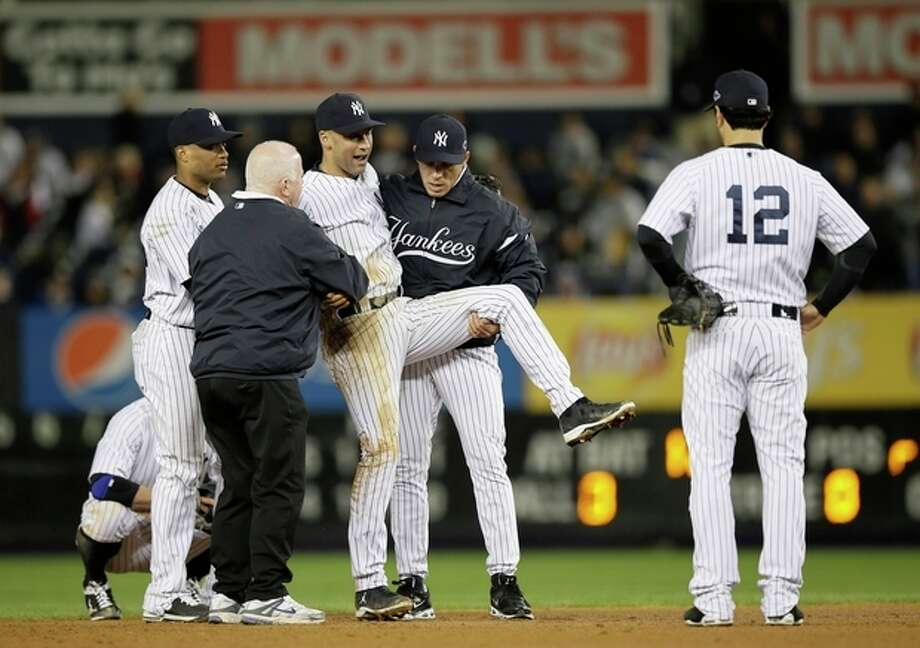 Trainer Steve Donohue, second from left, and New York Yankees manager Joe Girardi, second from right, help Derek Jeter off the field after he injured himself during Game 1 of the American League championship series against the Detroit Tigers Sunday, Oct. 14, 2012, in New York. New York Yankees' Robinson Cano, left, and Eric Chavez stood by. (AP Photo/Matt Slocum) / AP
