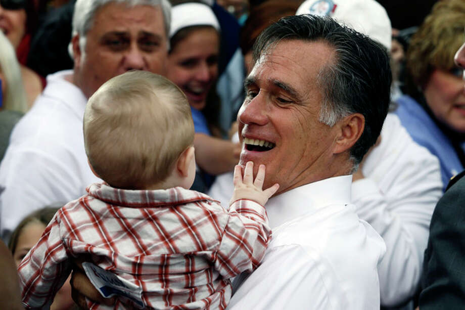 Republican presidential candidate and former Massachusetts Gov. Mitt Romney picks up a baby as he campaigns in front of The Golden Lamb Inn and Restaurant in Lebanon, Ohio, Saturday, Oct. 13, 2012. (AP Photo/Charles Dharapak) / AP