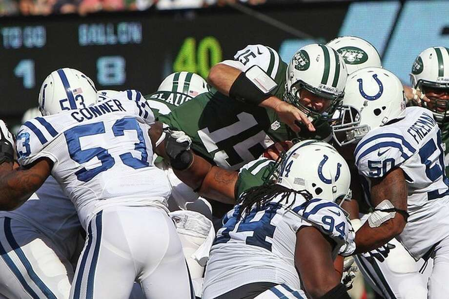 New York Jets quarterback Tim Tebow (15) dives for extra yards as Indianapolis Colts inside linebacker Kavell Conner (53), Drake Nevis (94) and Jerrell Freeman (50) tackle him during the first half of an NFL football game Sunday, Oct. 14, 2012, in East Rutherford, N.J. (AP Photo/Seth Wenig) / AP