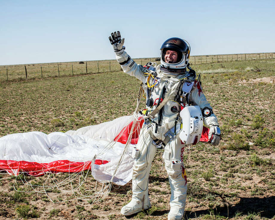 In this photo provided by Red Bull Stratos, Pilot Felix Baumgartner of Austria celebrates after successfully completing the final manned flight for Red Bull Stratos in Roswell, N.M., Sunday, Oct. 14, 2012. Baumgartner came down safely in the eastern New Mexico desert minutes about nine minutes after jumping from his capsule 128,097 feet, or roughly 24 miles, above Earth. (AP Photo/Red Bull Stratos, Balazs Gardi) / Red Bull Stratos