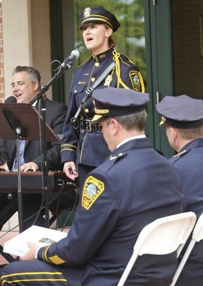 "Norwalk police detective Kristina LaPak and David harris sing ""The Prayer"" as police and residents commemorate the officers who died in the line of duty during the Norwalk Department of Police Services annual Police Memorial Service Friday.Hour photo / Erik Trautmann"