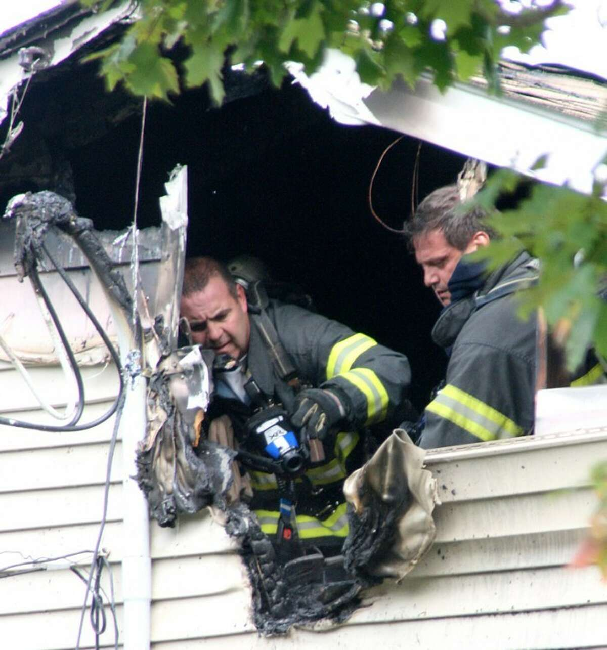 Photo by Chris Bosak Norwalk firefighters cut away wood and siding near the source of an electrical fire Monday morning on Country Club Road in Norwalk.