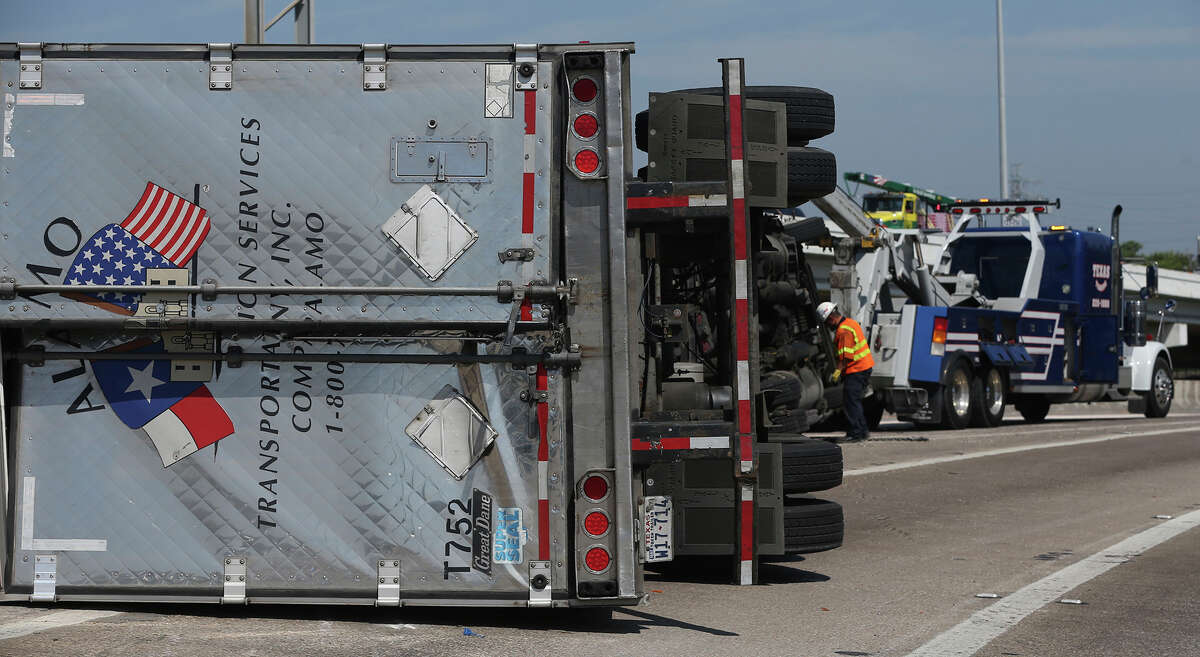 A crew works Wednesday June 15, 2016 to upright an 18-wheeler tractor trailer rig on the ramp connecting IH-35 south with IH-10 westbound near the Finesilver Building. Police at the scene said the driver was not injured and the truck was carrying flour or cornmeal in 50 pound bags. The freeway is closed in the area.