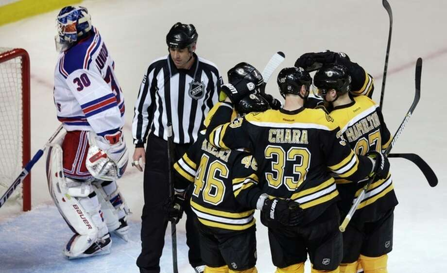 Boston Bruins defenseman Zdeno Chara (33) is congratulated by teammates after scoring against New York Rangers goalie Henrik Lundqvist (30) during the second period in Game 1 of an NHL hockey playoffs Eastern Conference semifinal game in Boston, Thursday, May 16, 2013. (AP Photo/Charles Krupa) / AP