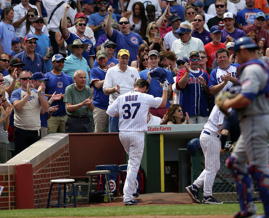 Chicago Cubs' Travis Wood tips his hat to the crowd after his two run home run in the fifth inning against the New York Mets in the MLB National League baseball game in Chicago on Sunday, May 19, 2013. (AP Photo/Charles Cherney) / FR170067 AP