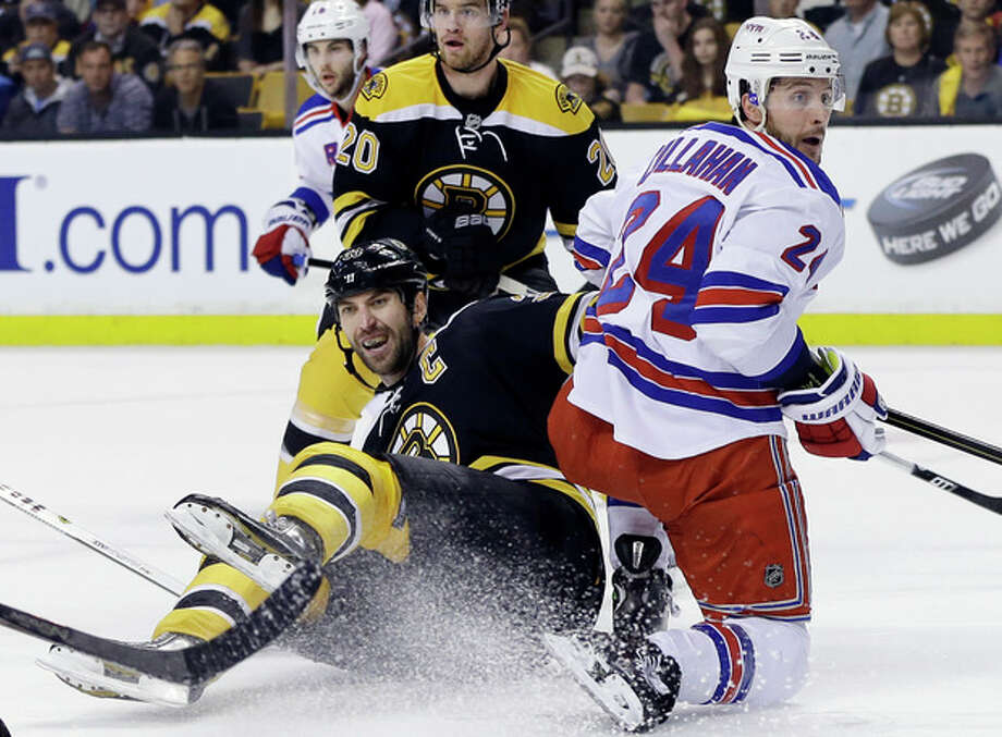 Boston Bruins defenseman Zdeno Chara, front left, goes down against New York Rangers right wing Ryan Callahan (24) as Bruins left wing Daniel Paille (20) looks on during the first period in Game 2 of the NHL Eastern Conference semifinal hockey playoff series in Boston, Sunday, May 19, 2013. (AP Photo/Elise Amendola) / AP