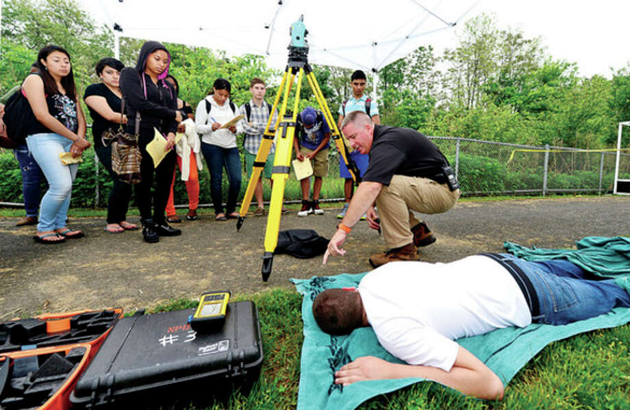 Lt. Art Weisgerger describes what signs to look for as the Norwalk Police Crime Scene Unit and Brien McMahon High School English teacher Bo Kane recreate the murder scene from the novel, Of Mice and Men, Thursday morning for BMHS classes.Hour photo / Erik Trautmann / (C)2013, The Hour Newspapers, all rights reserved