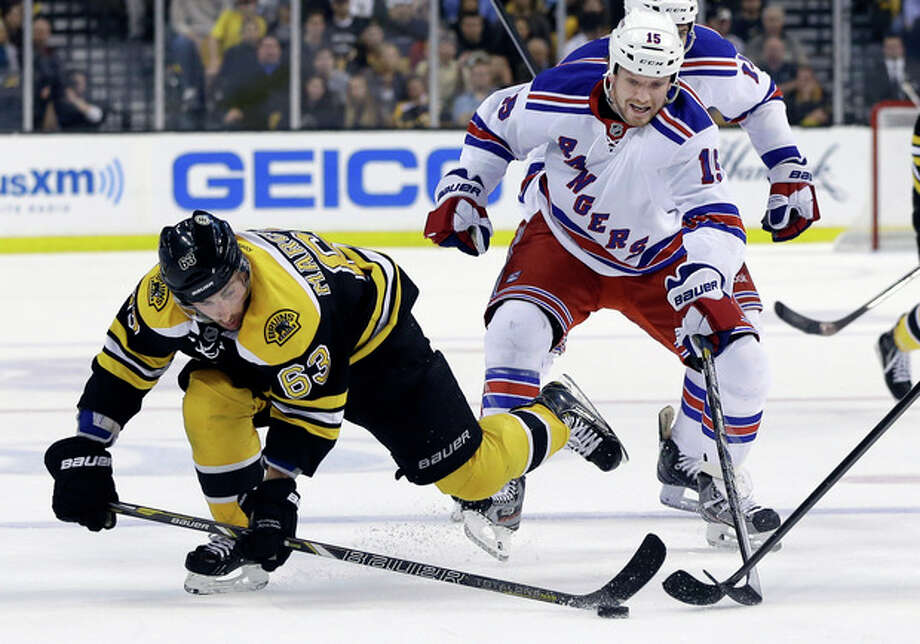 Boston Bruins left wing Brad Marchand (63) gets to the puck ahead of New York Rangers right wing Derek Dorsett (15) during the second period in Game 2 of the NHL Eastern Conference semifinal hockey playoff series in Boston, Sunday, May 19, 2013. (AP Photo/Elise Amendola) / AP