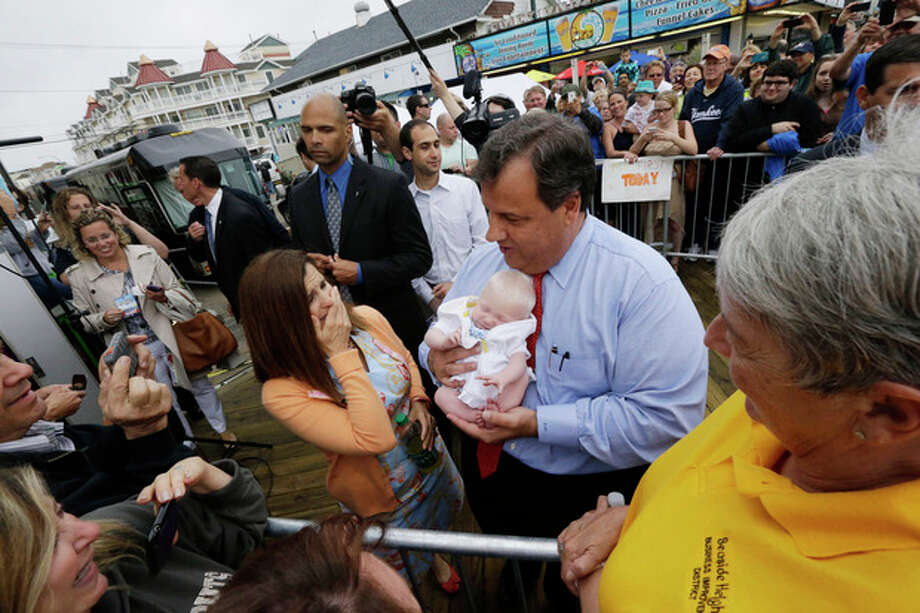 New Jersey Gov. Chris Christie, right, holds 6-week-old Willow DeParre, as first lady Mary Pat Christie looks on as they greet people during the opening of the New Jersey shore, Friday, May 24, 2013, in Seaside Heights, N.J. Christie cut a ribbon to symbolically reopen the state's shore for the summer season, seven months after being devastated by Superstorm Sandy. Several beach communities have annual beach ribbon cuttings, announcing they are back in business. But this year's ceremonies are more poignant seven months after a storm that did an estimated $37 billion of damage in the state. (AP Photo/Julio Cortez) / AP