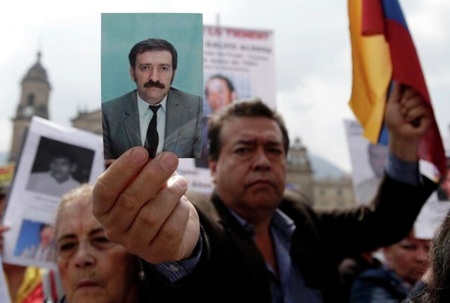 A man shows a photo of a missing person during a protest organized by activists and relatives of people allegedly disappeared by rebels, in Bogota, Colombia, Sunday, Oct. 14, 2012. Demonstrators demanded participation in the peace talks between Colombia's government and Colombia's main leftist rebel movement, FARC, that will start on Monday in Norway. (AP Photo/Fernando Vergara) / AP