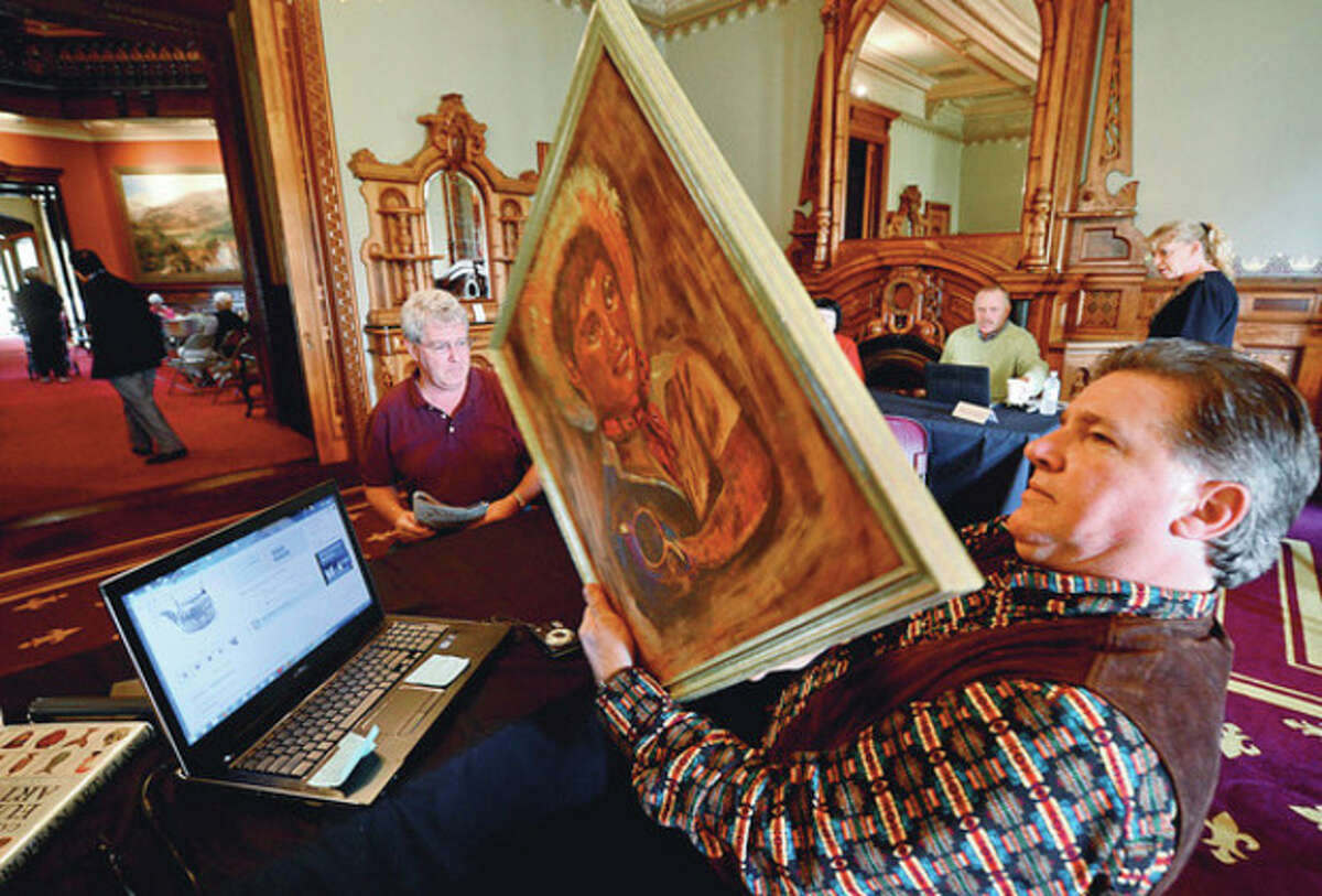 Kevin McClellan appraises a painting for Bob Sullivan at The Lockwood-Mathews Mansion Museum's annual Antiques Appraisal Weekend and Vintage & Designer Jewelry Sale Saturday. Hour photo / Erik Trautmann