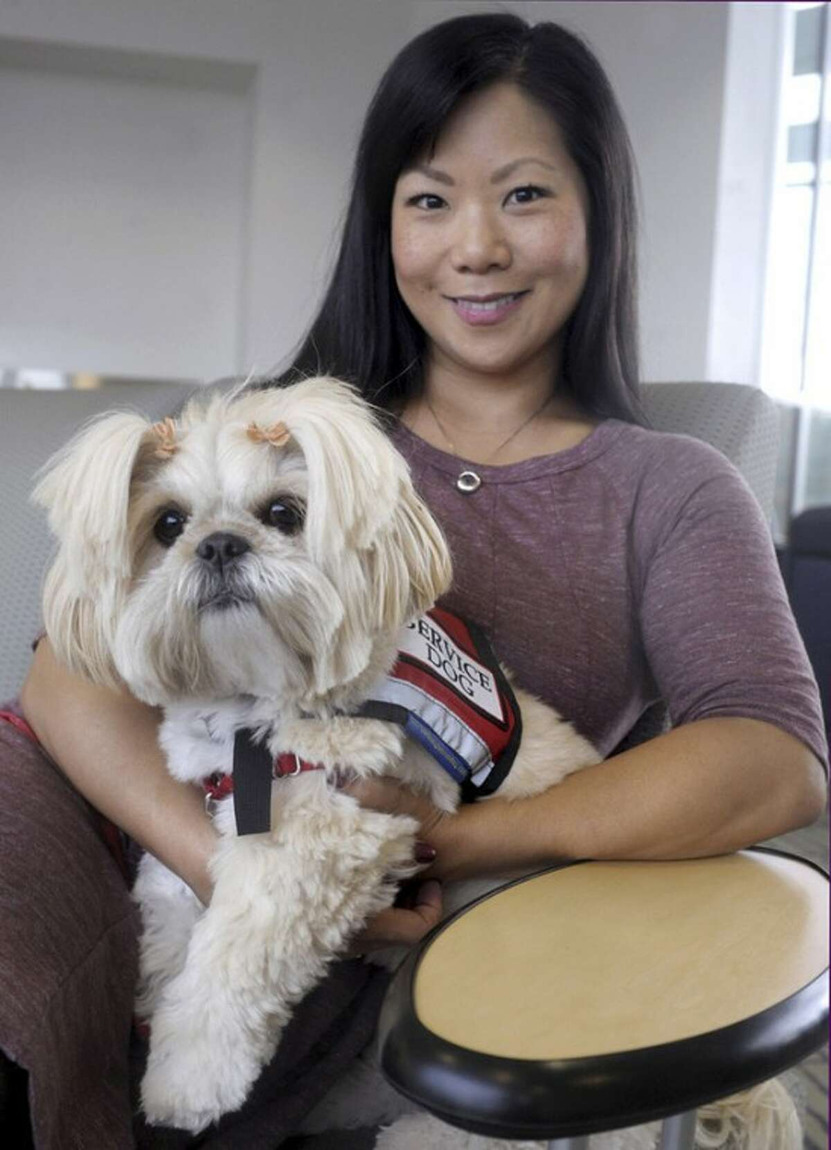 AP Photo/Journal Inquirer, Jim Michaud Staff Sgt. Sandra Lee poses for a photograph with her service dog Emma in Manchester.
