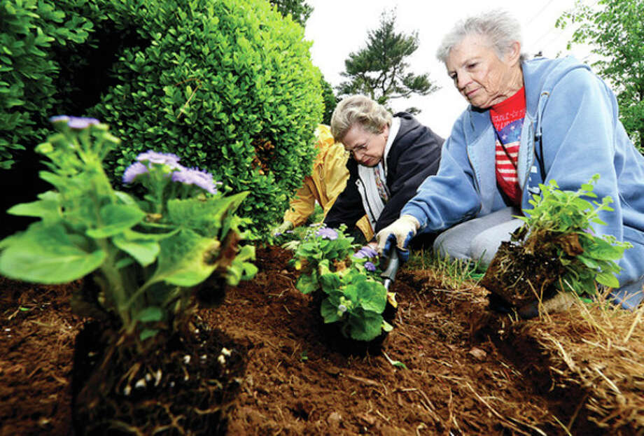 Members of the Norwalk Garden Club including Betsy Kondub and Janet Valus gather on the Norwalk Green to plant seasonal flowers around the flagpole and the cannon Tuesday.Hour photo / Erik Trautmann / (C)2013, The Hour Newspapers, all rights reserved