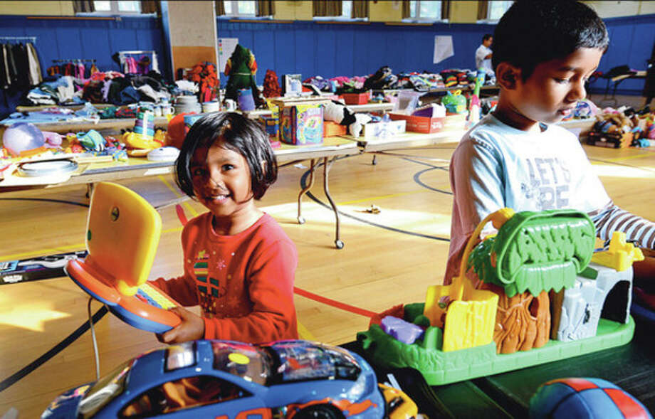 Hour photos / Erik TrautmannBargain shoppingAbove, Jeslin and Johan Prince look for toys at the Tracey Elementary School's annual tag sale fundraiser Saturday. Right, Kathy Gilbertie looks for items. / (C)2012, The Hour Newspapers, all rights reserved