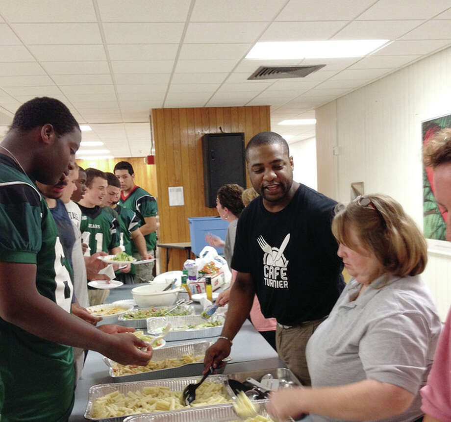 Contributed photoErnst Turnier, center, and Monica Arcario dish up food to Norwalk High football players at Thursday's pasta dinner. Turnier has put on a few of the dinners for the Bears' football team.