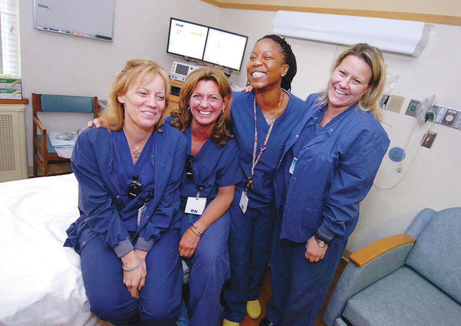 Hour Photo/Alex von KleydorffPart of the Norwalk Hospital Labor and Delivery Team, registered nurses (left to right) Melinda Dasher, Linda Starr, Heidi Stellar and Wendy Finch share a relaxed moment in one of the labor rooms. / 2013 The Hour Newspapers