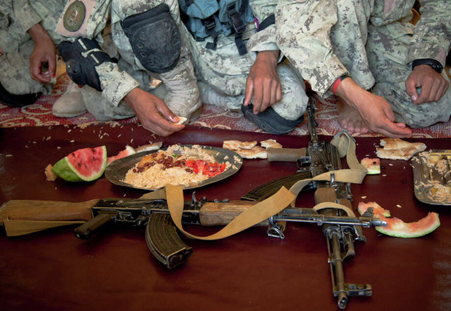 Afghan National Police lay down their guns during lunch time at their base in Marjah, Helmand Province, Afghanistan, Friday, Oct 19, 2012. Afghanistan's police are routinely targeted by insurgent attacks in southern Afghanistan, one of the deadliest regions in the country. (AP Photo/Anja Niedringhaus) / AP